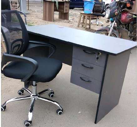 An office table combined with a black adjustable mesh chair image 1