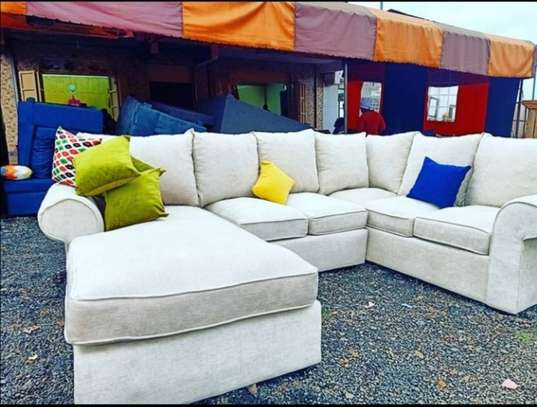 A white l-shaped 7 seater couch back pillowed. image 1