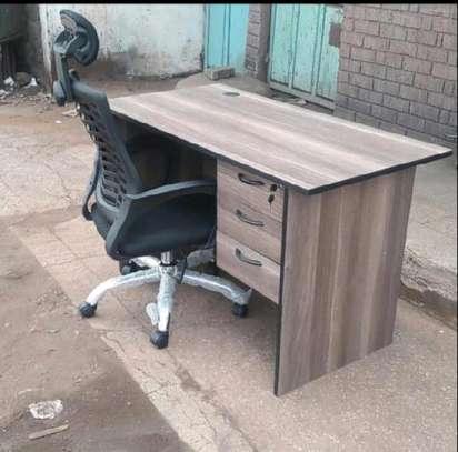 An office desk with a lumbar support headrest chair image 1