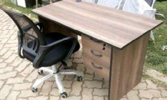 An office desk with a lack lipping on edges and a desk chair as a package image 1