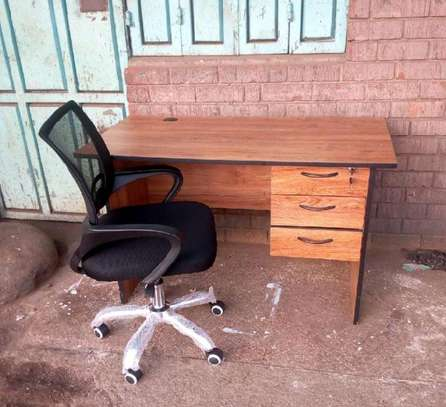 An office desk stable and sturdy comes with a mesh chair image 1