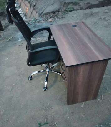 An adjustable office chair with an office table image 1