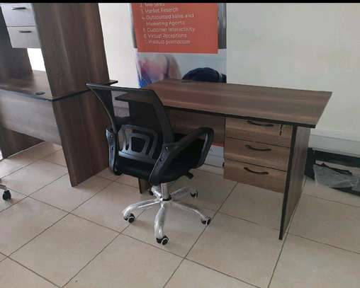 An office desk of 21st century with a black swivel chair image 1