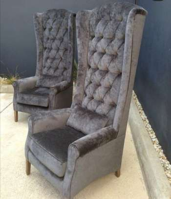 A grey wing chair. image 1