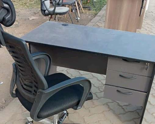An office desk with a reclining and adjustable headrest chair image 1