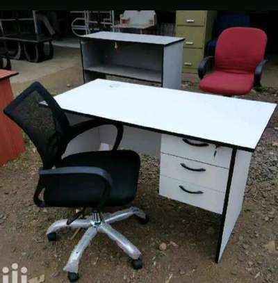 An office desk table with a grommet passing cables and a black mesh office seat image 1