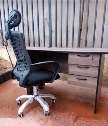 An office desk with high back chair of black armrest image 1