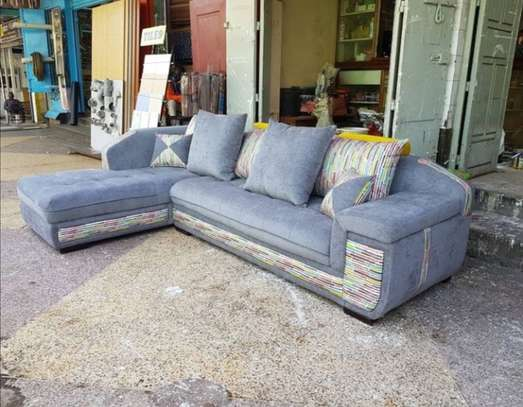 Grey white l-shaped five seater back pillowed. image 1