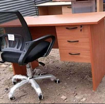 A swivel black chair with a standing working desk image 1