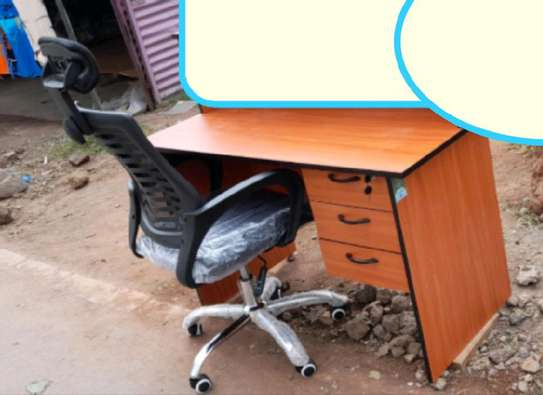 An office desk with a high back black headrest chair image 1