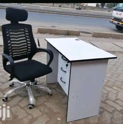 An office table with a grommet for cables entry and a headrest office chair image 1