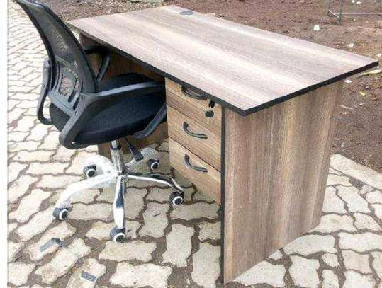 An office desk in conjunction with a black fabric swivel chair image 1
