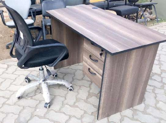 An office/home desk with a black coloured mesh chair image 1