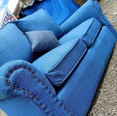 Light blue two seater back pillowed sofa. image 1