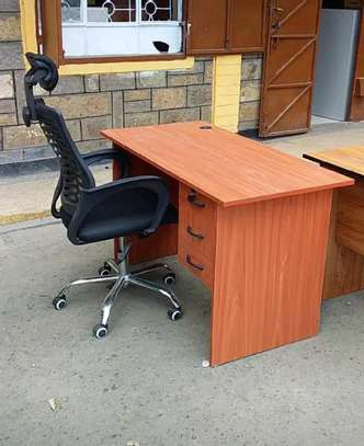An office desk with adjustable black headrest chair with 5 wheels image 1