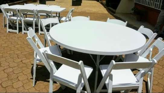 white foldable chairs, round and rectangle tables