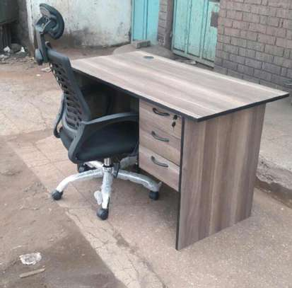An office desk with an adjustable black headrest chair image 1