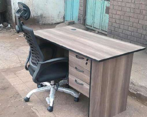An office table with a laptop use chair in black image 1