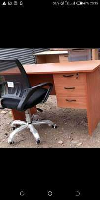 An office desk with a classic office chair of which is adjustable image 1